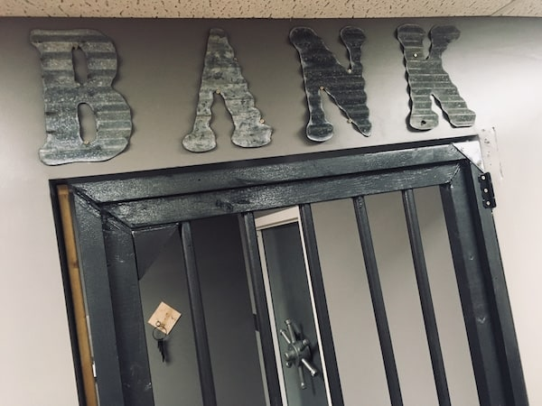 "In-game: The word ""BANK"" cut from corrugated Aluminum. Below it is a barred door and beyond it, a vault door."