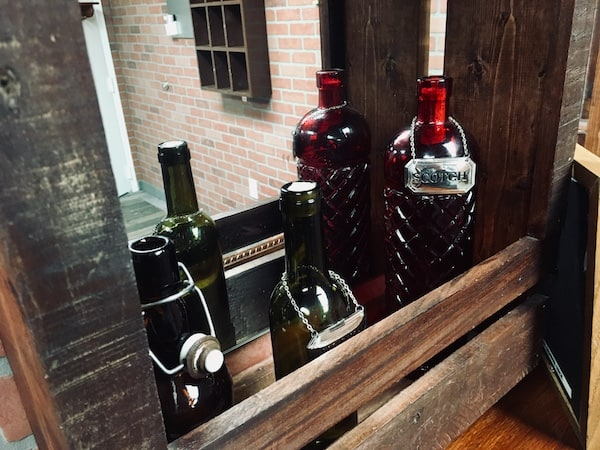 In-game: Closeup of a small bar featuring old liquor bottles.