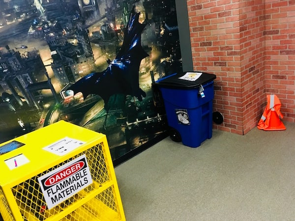 """In-game: A yellow cage labeled """"flammable materials"""" a garbage can, an orange traffic cone, and an oversized wall decal of a screenshot from the Batman from Arkham Knight video game."""