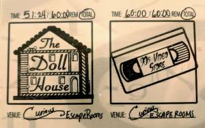 The stamps for both of Curious Escape Rooms' games, the Doll House & The 90s Video Store.
