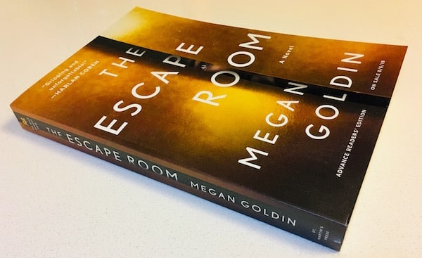 "The gold covered novel for ""The Escape Room"" by Megan Golden. There is a person peering through a narrowly opened door."