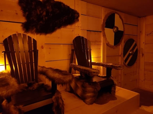 In-game: The inside of a cabin with two wood and fur thrones surrounded by round shields.