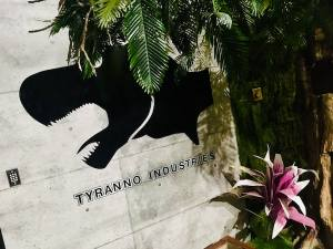 In-game: The Tryanno Industries logo on a concrete building in a tropical setting.