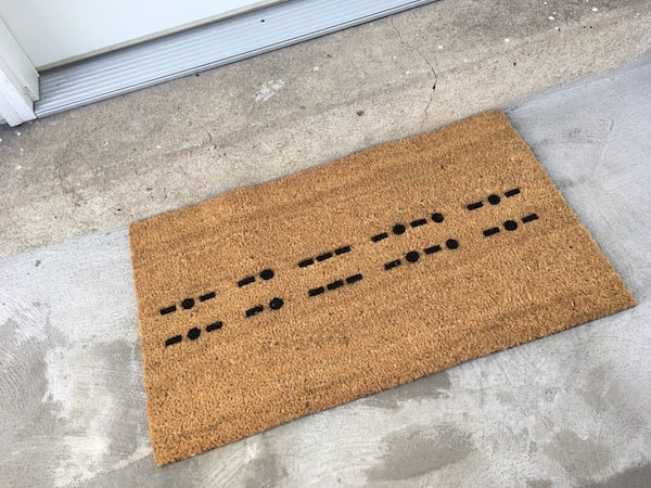 Morse code welcome mat reads, -.- -. --- -.-. -.-, -.- -. --- -.-. -.-.