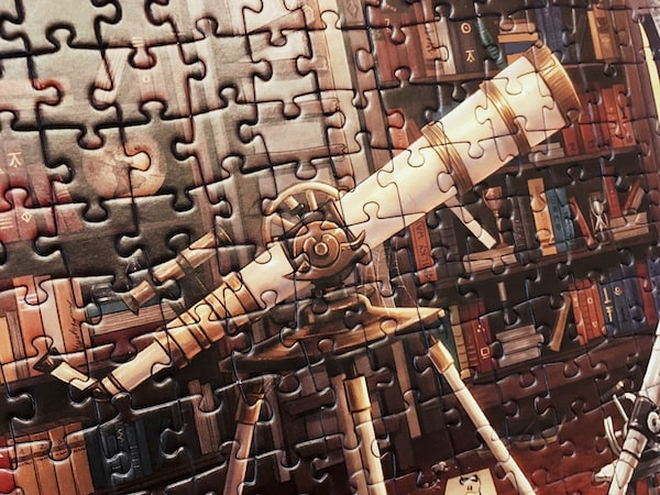 Portion of an assembled jigsaw puzzle featuring a beautiful telescope in a warm book-filled study.