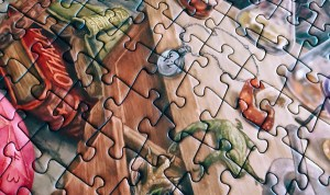 Portion of an assembled jigsaw puzzle featuring a magical books and ingredients.