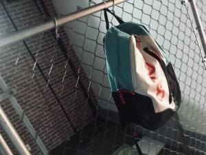 In-game: A schoolyard fence with with a bookbag hanging from it.