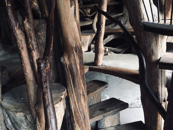 A wooden spiral staircase made from whole trees.