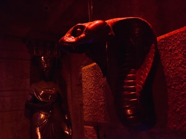In-game: A statue of a cobra's head protruding from the sandstone wall of a tomb.
