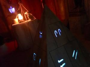 In-game: A pyramid with glowing symbols in the middle of a tomb excavation site.