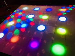 In-game: a dance floor with colored lights shining on it.