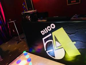 """In-game: the DJ booth labeled """"Disco 54."""""""