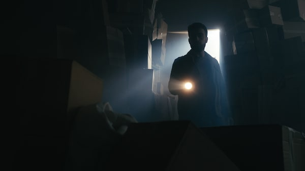 A man with a flashlight searching a storage space filled with cardboard boxes.