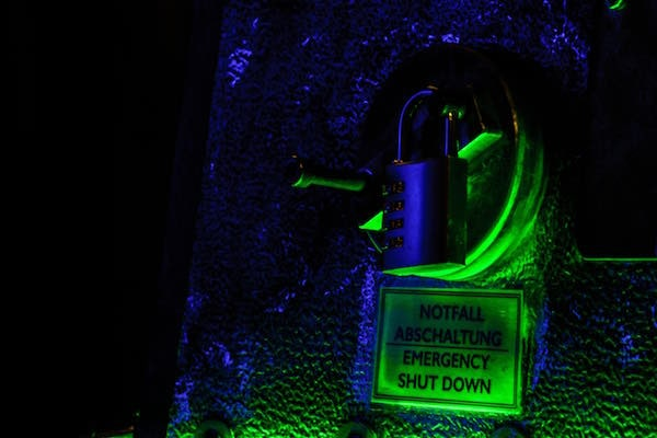 """In-game: a padlock on a piece of worn machinery labeled """"Emergency Shut Down"""" in a dark room."""