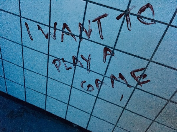 "In-game: ""I want to play a game"" painted in blood on a white tiled wall."