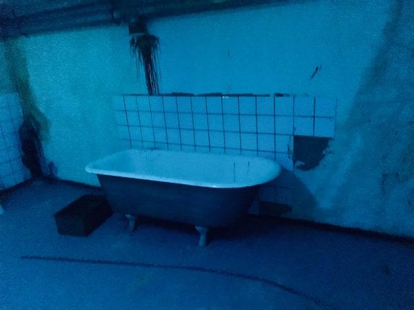 In-game: An iron clawed bathtub in a rundown bathroom.