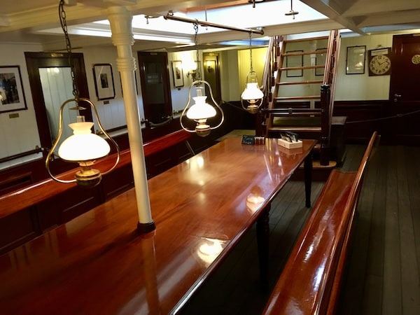 A beautiful long wooden table in the middle of the crew's quarters.