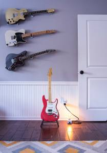 A room with 4 electric guitars, a single light bulb, and a door.