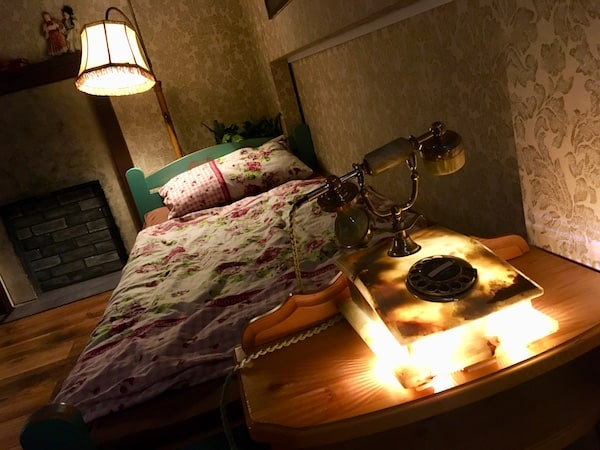 In-game: A glowing rotary phone ad the foot of a bed.