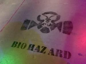 "In-game: ""Biohazard"" and an image of a gasmask painted in black on concrete."