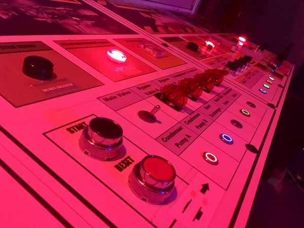 In-game: Nuclear reactor control panel covered in buttons, switches, and lights.