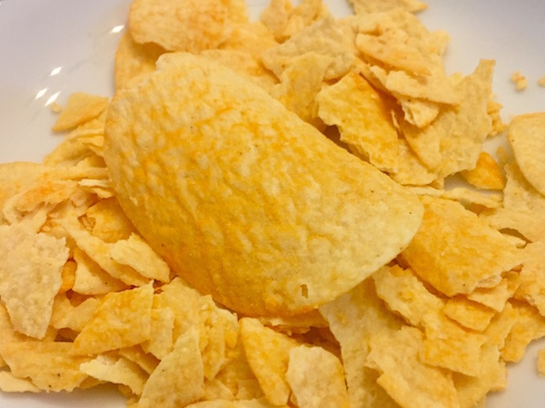 One whole, unbroken mystery flavor Pringle resting on a bed of broken chips. The chips have an orangey appearance.