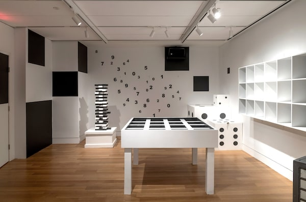 In-game: a black and white room with numbers on the wall, a large gridded table, oversized dice, and a tall jenga-like tower.