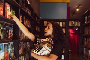 A person holding many movies reaching up for a movie on the shelf of a video store.