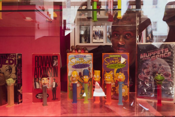 A person reaching into a display case with movie boxes and pez dispensers that correspond to the characters featured on those boxes.