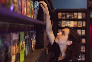 A person reaching up for a movie on the shelf of a video store.
