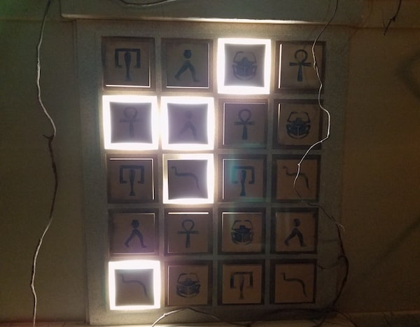 A grid of tiles depicting different hieroglyphics, with several squares lit up.