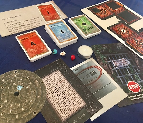 In-game: An assortment of card decks, paper props, a tea candle, and multicolored skulls.