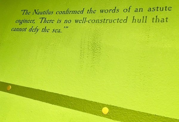 "In-game: a quote from ""20,000 Leagues Under the Sea""painted to the wall: ""The Nautilus confirmed the words of an astute engineer, 'There is no well-constructed hull that cannot defy the sea."""