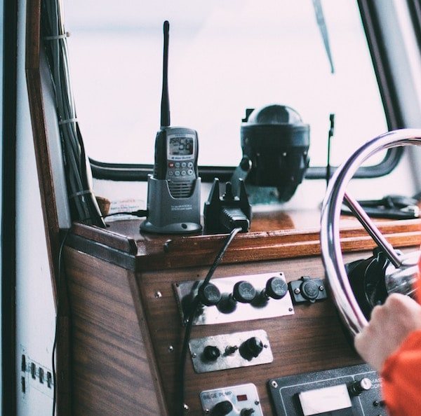 A walkie talkie in a cradle at the controls for a boat.