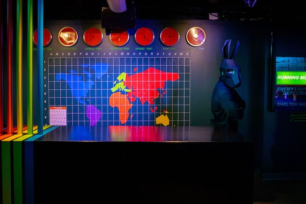In-game: a character in a black rabbit costume standing before a multi-colored world map.