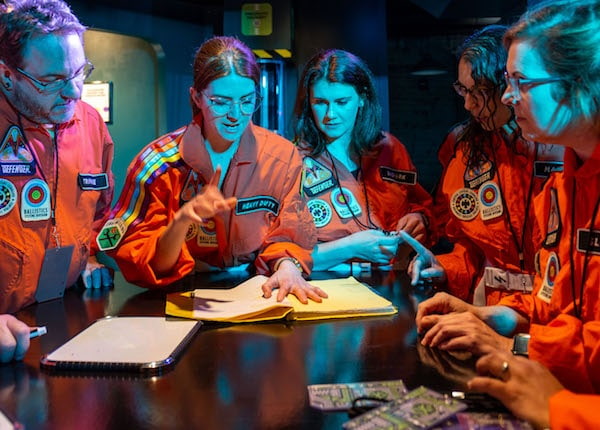 In-game: 5 players in orange flightsuits working on a puzzle.