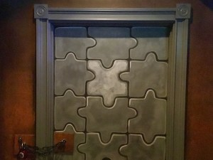In-game: closeup of a gray door pained like a jigsaw puzzle and chained shut.