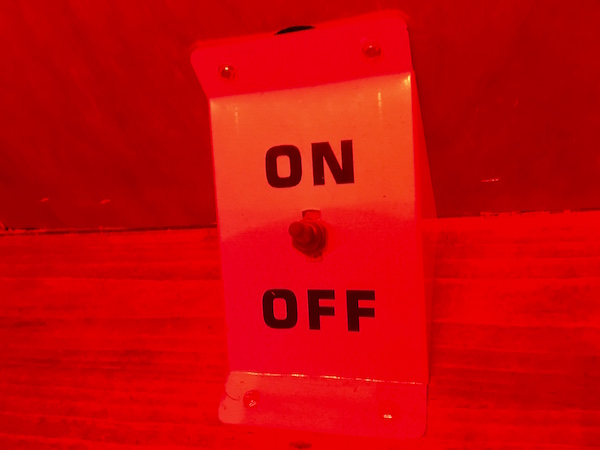 In-game: closeup of a red on/ off switch.