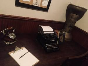 In-game: A desk with an old typewriter, a book, a phone, and an ancient egyptian artifact.
