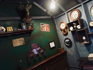 In-game: another view of Kazam's study, the wall is covered in clocks and a strange mechanism is mounted to the wall.