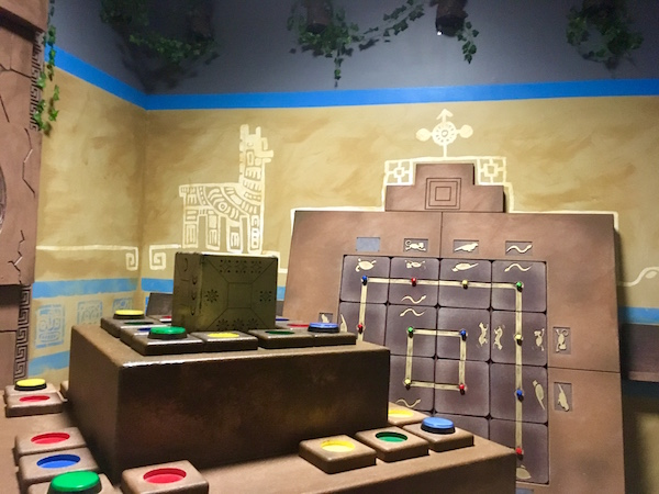 In-game: wide angle view of the Mayan tomb, a pyramid in the middle of hte room, an large wall mounted puzzle beyond it.