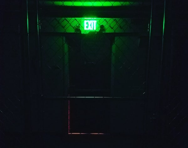 In-game: A glowing green exit sign over a door viewed through a chainlink fence.