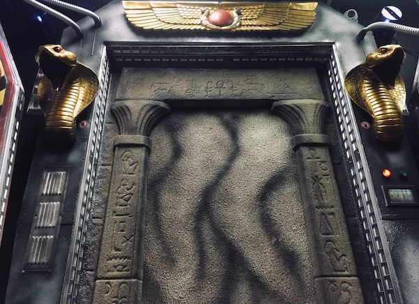 In-game: A sealed stone doorway to an ancient Egyptian tomb flanked by king cobra statues and asurrounded by strange technology.