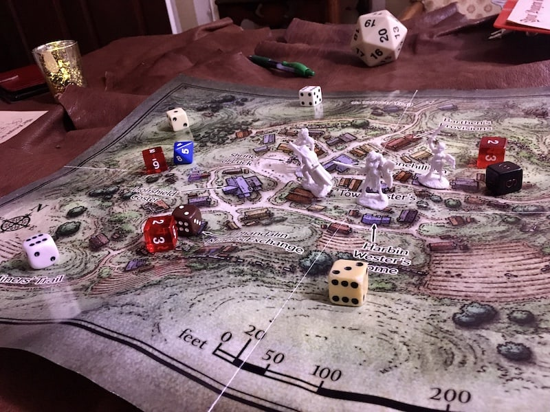 The game map covered in dice with our chraacter models in the town.