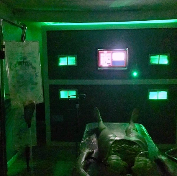 In-game: A dead person on an operating table in a green lit room, their organs are exposed.