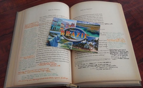 "Sample pages of Ship of Theseus, along with a postcard that says ""Greetings from Brazil."""
