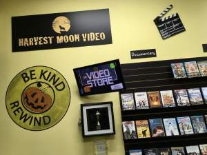 """In-game: The Harvest Moon Video logo beside a large sign that reads, """"Be kind rewind."""""""