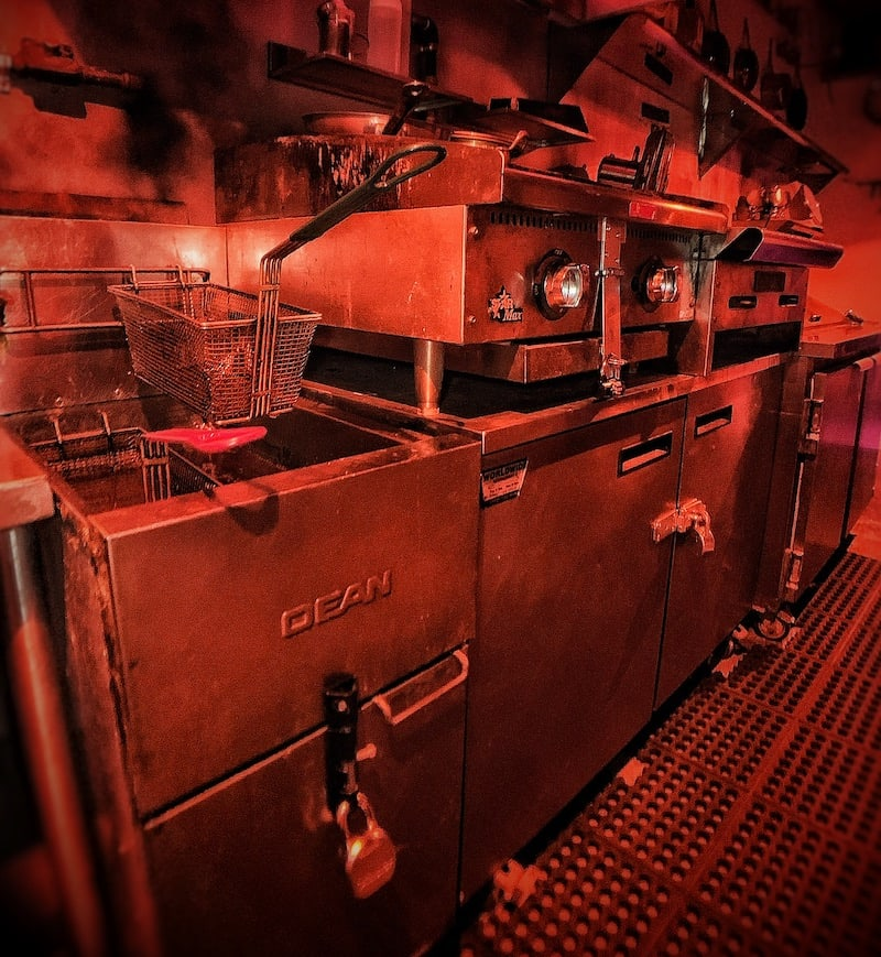 In-game: A red tinged view of an restaurant kitchen.