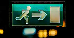 A green exit sign with a person approaching a door.