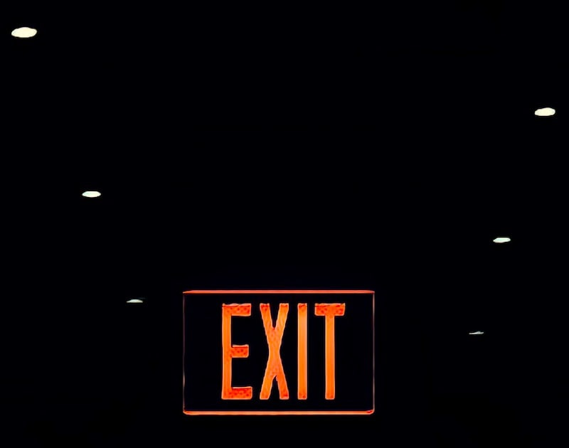 "A red sign reads ""Exit"" glowing in the darkness."